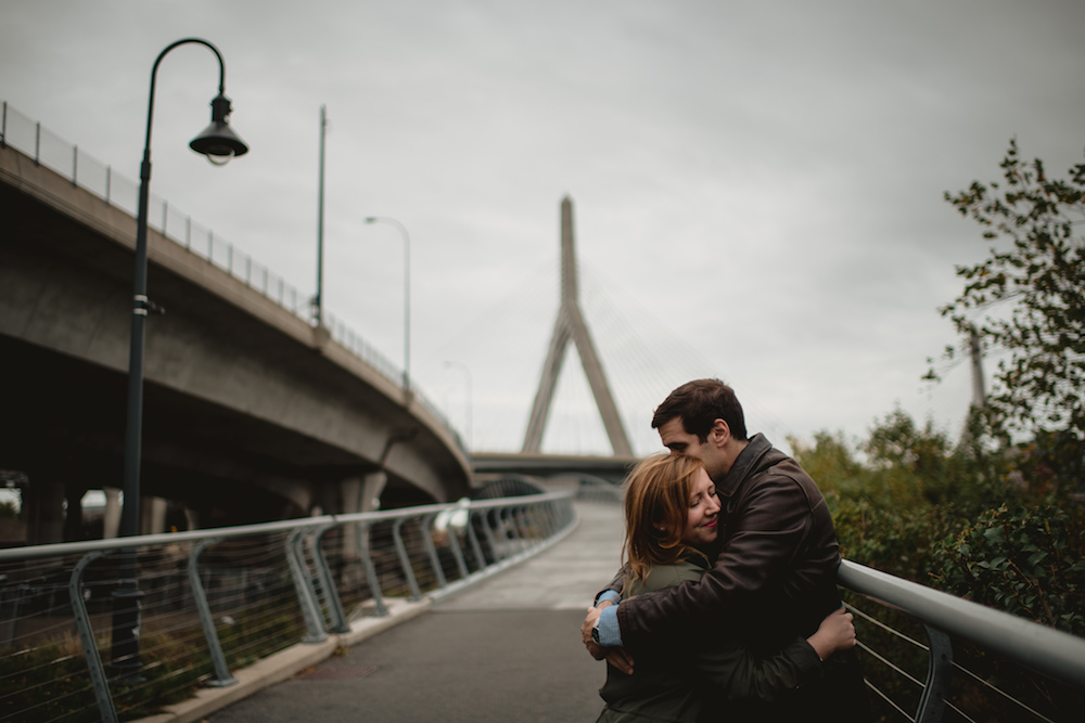 Chris and Katie embracing in front of a bridge